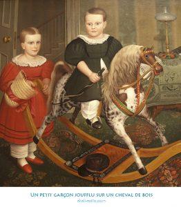 Un petit garçon joufflu sur un cheval de bois